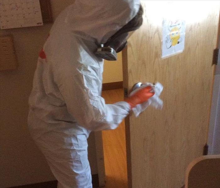 Man in PPE cleaning a door in a commercial facility